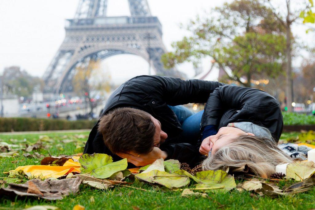 Ensaio na Torre Eiffel por fotografo brasileiro em Paris que registra casal deitado na grama no Trocadéro durante outono